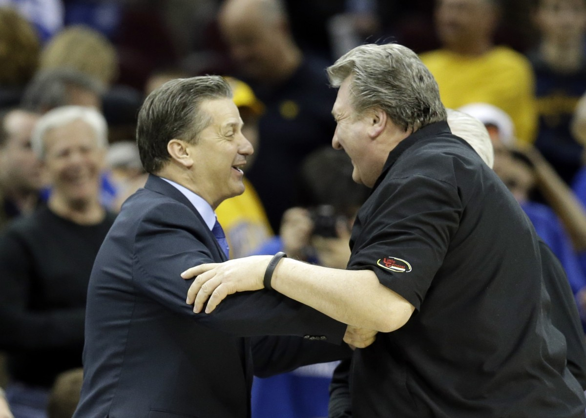 Bob Huggins and John Calipari, clutching arms and smiling together as crowd looks on.