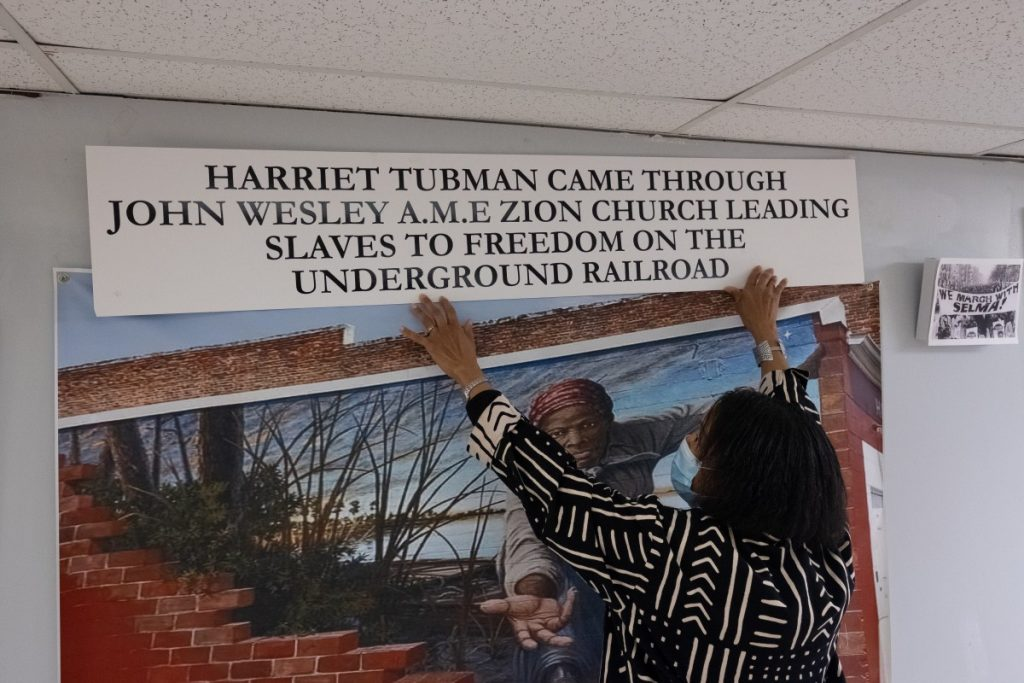 Dr. Norma Thomas holds up a sign above a printed mural featuring American abolitionist Harriet Tubman. Thomas hopes to secure funding for renovations to the church so that she can permanently install her Black history museum in its basement. Photo: Justin Hayhurst/100 Days in Appalachia