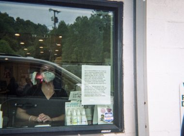 """Valerie Akers, co-owner of the Parkview Pharmacy is seen through a plexiglass window as Mary Slone lifts her disposable camera to her face. """"While I cannot remember the exact reason for me being there, I do recall the surrealness of visiting the pharmacy I patronized but doing so via drive-through. Even with plexi glass between us, we were both wearing masks. It truly was a moment out of the science fiction stories that I have long read,"""" Slone recalled. Photo: Mary Slone, Provided"""