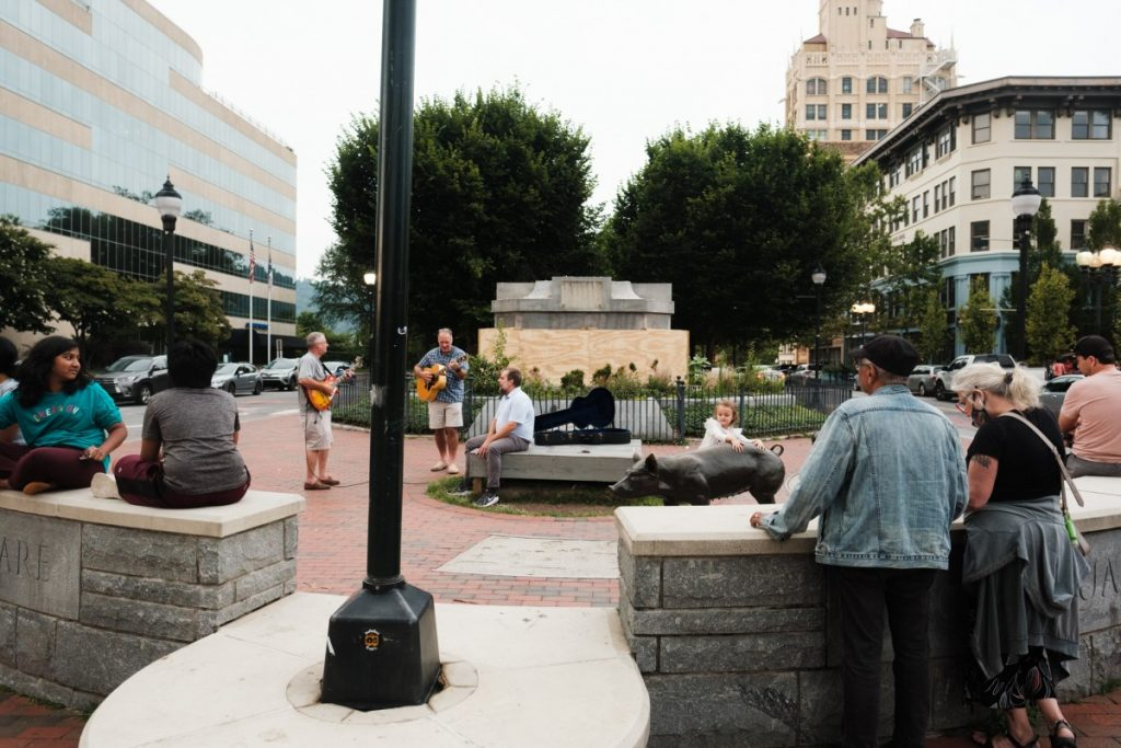 What's left of Vance Monument sits in the background of people gathered at Pack Square in Asheville, North Carolina. The obelisk that sat atop the base seen here was removed in early May. Photo: Hunter Rentz/100 Days in Appalachia
