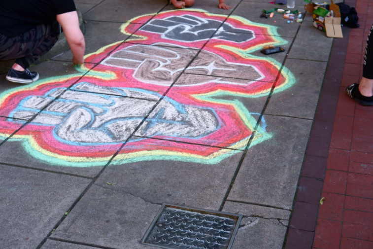 """Over days and weeks, the protests on the Chambersburg Square grew and evolved. A few days in, some people began to use art to express their emotions and goals for the community. Chalk art was created with an """"all hands on deck"""" approach; everyone from practicing artists to curious toddlers participated. Photo: Madison Mellinger"""